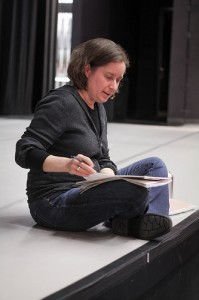 photo of director Alison Humphrey sitting cross-legged during a rehearsal