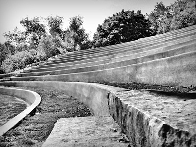 black and white photo of the stone seats of an amphitheatre